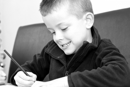 young boy drawing with pencils on a table photo