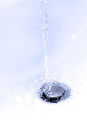 water running down a bathroom sink plug hole Stock Photo - 16803334