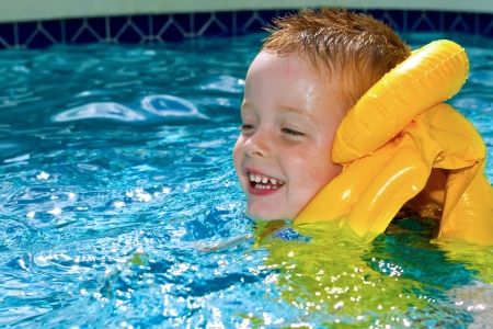 little boy swimming with life vest on Stock Photo