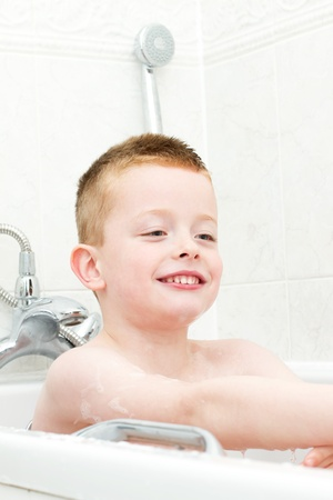 little boy washing in the bath photo