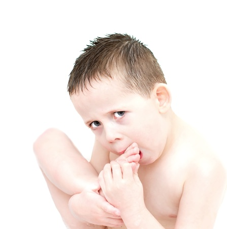 little boy eating biting his toes