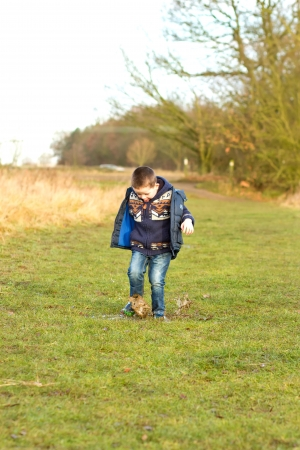 little boy splashing in a puddle in the field photo