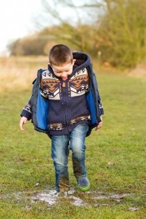little boy splashing in a puddle in the field