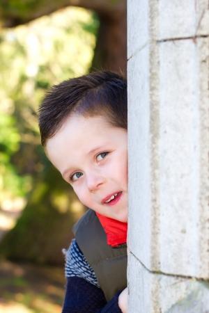 happy little boy peeping around a corner