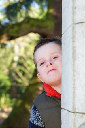 young boy smiling: Happy young boy smiling in an outdoor scene Stock Photo