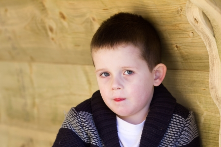 Depressed young boy looking directly ahead photo