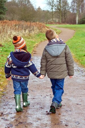 brothers holding hands on a country path photo