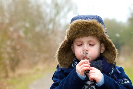 young boy blowing seeds on a cold winters day photo