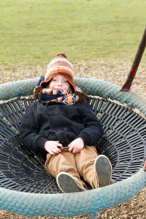 happy young boy playing at the park on a cold day photo