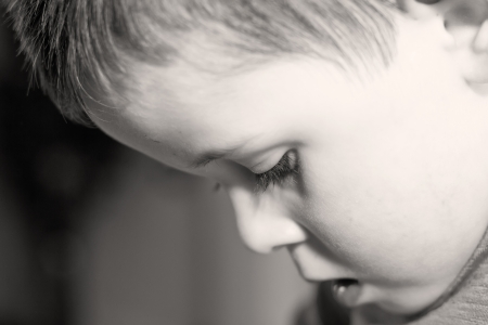 depressed little boy looking down photo
