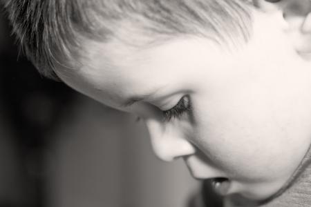 depressed little boy looking down