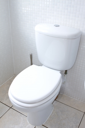 white toilet in a clean white tiled bathroom