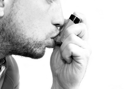 man inhaling his asthma pump Stock Photo
