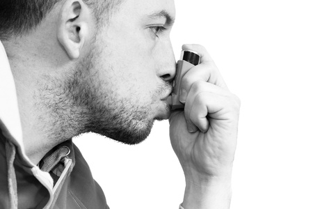 inhaling: man inhaling his asthma pump Stock Photo