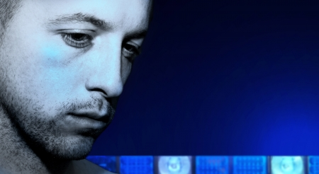 criminal looking down with blue lights from police car in the background Stock Photo