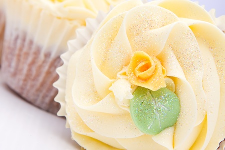 homemade creamy luxury cup cakes with detailed flower and sparkles photo