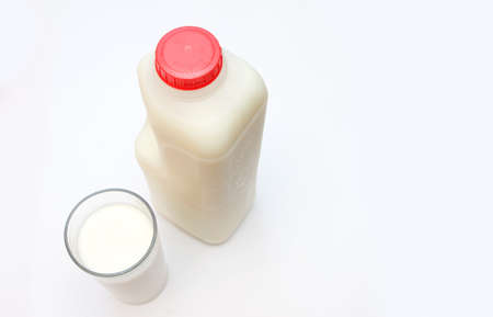 glass of milk with carton behind photo