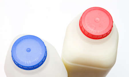 skimmed and full fat milk in containers photo