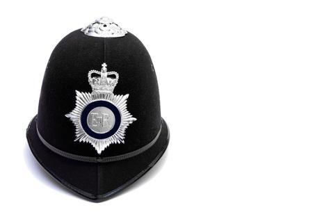 gorra polic�a: custodia policial brit�nico hemet tradicional en blanco Foto de archivo