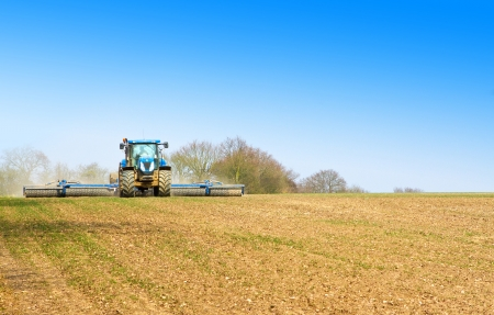 blue tractor ploughing the fields in spring Stock Photo