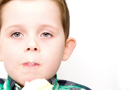 handsome little boy eating a fresh cream cup cake with messy face photo