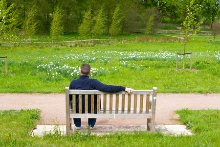 man sitting on a bench in a countryside scene photo