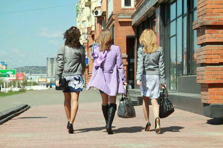Three girls walking on the street.