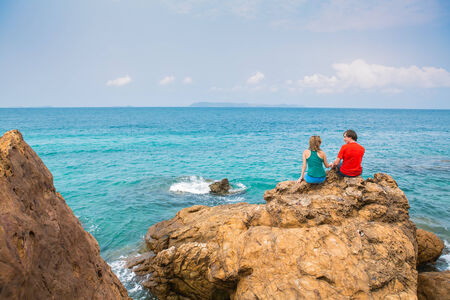 A couple seats on the rocks in front of the sea photo