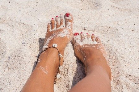 painted toes: Relaxing feet on the white sand. Stock Photo