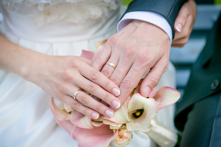 Hands of the bride and groom on the wedding bouquet Archivio Fotografico