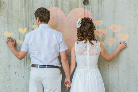 Back view of  bride and groom infront of the wall with pink heart. Stock Photo