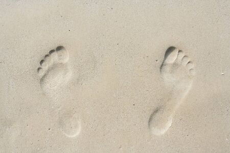 Footprint on the wet yellow sand next to the sea Stock Photo
