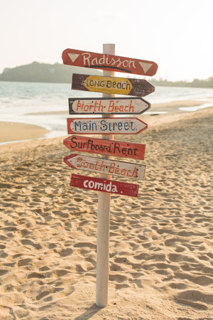 Signpost made of wood with the on the tropical beach in Thailand.