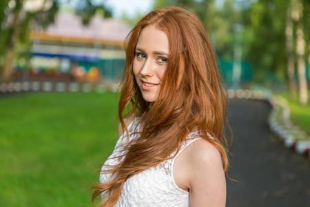 red hair girl: Portrait of young modern girl with bright red hair on the background of nature.