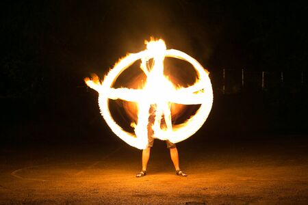 Fire-show man in action in night time. Stock Photo