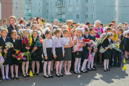 schoolyard: NOVOKUZNETSK, KEMEROVO REGION, RUSSIA - SEP, 1, 2014: Meeting with the first-grade pupils and teacher at schoolyard. The day of knowledge in Russia. Editorial