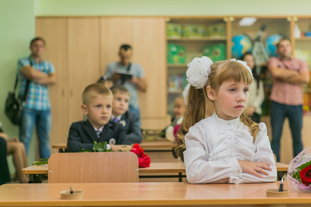 first day of school: NOVOKUZNETSK, KEMEROVO REGION, RUSSIA - SEP, 1, 2014: First-grade students and teacher are in school classroom at first lesson. The day of knowledge in Russia.