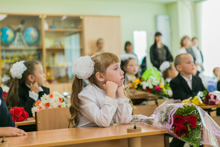 knowledge: NOVOKUZNETSK, KEMEROVO REGION, RUSSIA - SEP, 1, 2014: First-grade students and teacher are in school classroom at first lesson. The day of knowledge in Russia.