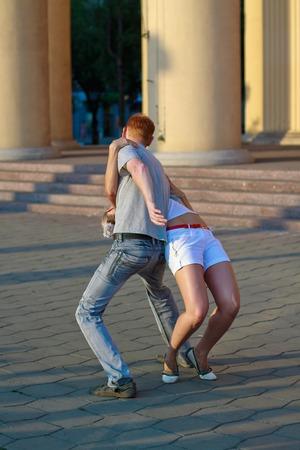 Novokuznetsk, Kemerovo REGIÓN, 24 RUSIA-JUNIO DE 2012 :: Una pareja de hombre y mujer están bailando baile social en la calle en un día soleado de verano.