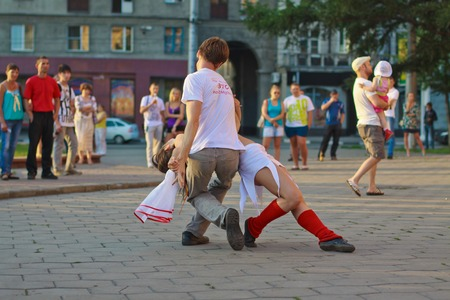 hustle: NOVOKUZNETSK, KEMEROVO REGION, RUSSIA-JUNE 24, 2012 ::  A couple of young man and woman are dancing social dance on the street in a sunny summer day. Editorial