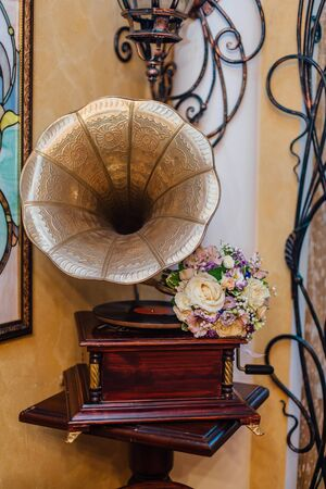 phonograph: Beautiful wedding bouquet lays on the phonograph.