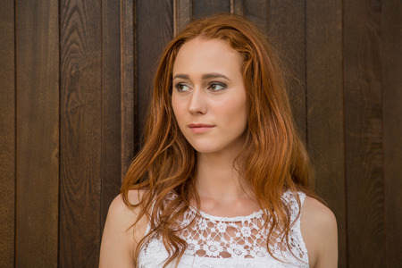 quadrant: Portrait of young modern girl with bright red hair on the background of old wooden door. Stock Photo
