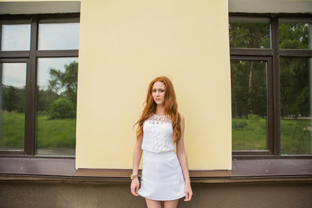 quadrant: Portrait of young modern girl with bright red hair between two windows