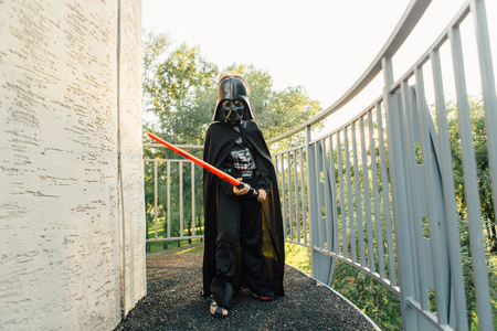 starwars: NOVOKUZNETSK, KEMEROVO REGION, RUSSIA - AUGUST 19, 2015 :: Boy in a costume of  Darth Vader with sword from the movie Star Wars in the park.