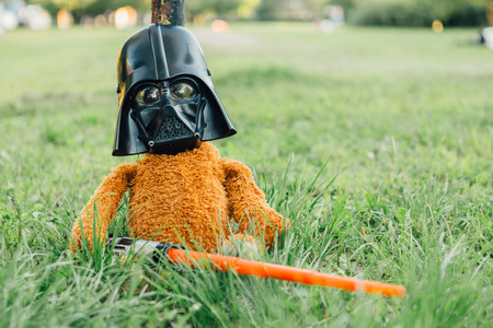 starwars: NOVOKUZNETSK, KEMEROVO REGION, RUSSIA - AUGUST 19, 2015 ::  Teddy bear in a msk of Darth Vader with sword from the movie Star Wars in the park.
