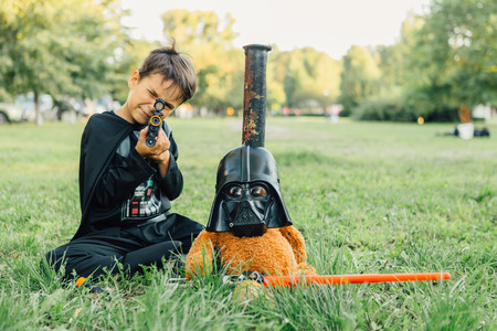 starwars: NOVOKUZNETSK, KEMEROVO REGION, RUSSIA - AUGUST 19, 2015 :: Boy in a costume of  Darth Vader and Teddy bear in a mask of Darth Vader with sword
