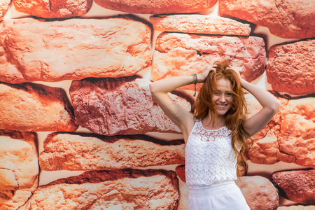 quadrant: Portrait of young modern girl with bright red hair on the background of printed stones. Stock Photo
