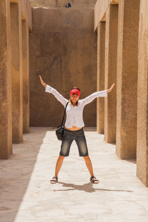 cheops: Happy tourist girl near the ruins of Giza in Cairo, Egypt.