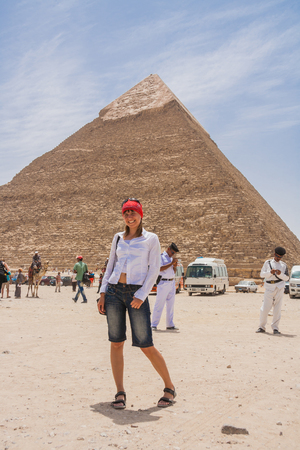 take a history: Giza, Cairo, Egypt - June 03, 2010 :: Happy tourist girl and pyramid of Giza in Cairo, Egypt. Editorial