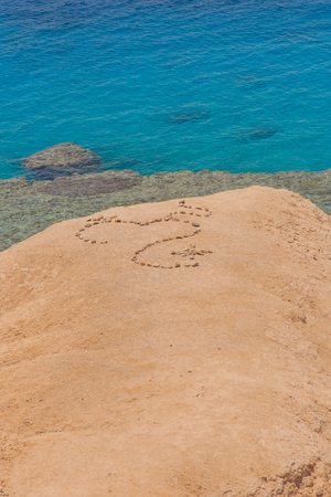 loveheart: Love heart shape on sand made of stones, symbol of love on the background of the blue sea.